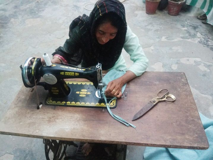 A woman in the Indian state of Madhya Pradesh sews a face mask.