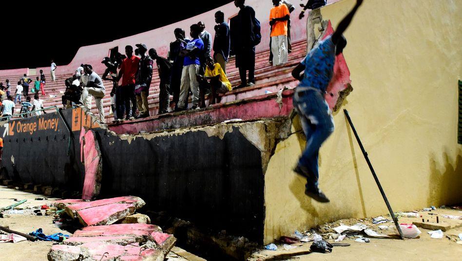 Menschen an der eingestürzten Wand im Demba-Diop-Stadion in Dakar