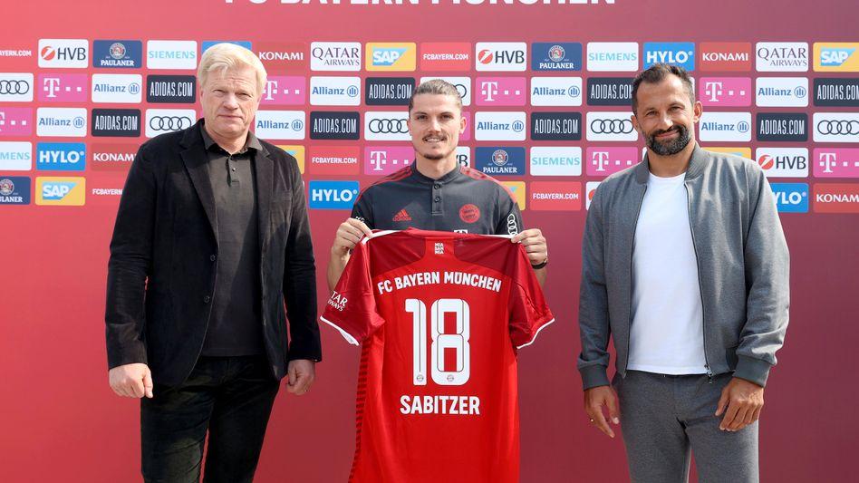 Marcel Sabitzer (Mitte) wurde am Donnerstag als neuer Spieler des FC Bayern von Bayern-Vorstandschef Oliver Kahn (links) und Sportvorstand Hasan Salihamidžić vorgestellt