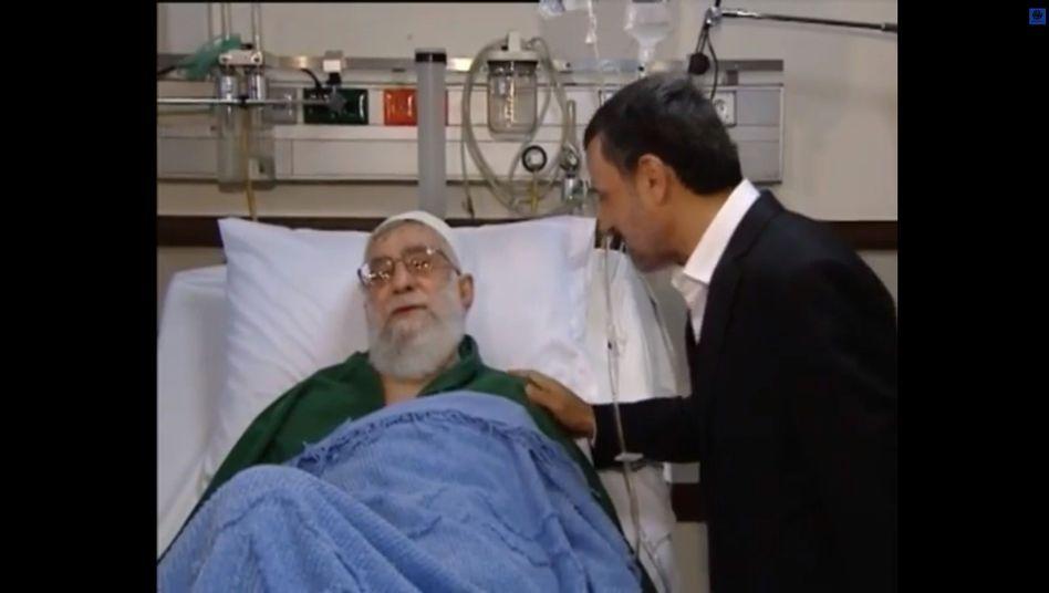 Unwillkommener Besuch: Mahmud Ahmadinedschad schaut beim frisch operierten Ajatollah Ali Chamenei vorbei