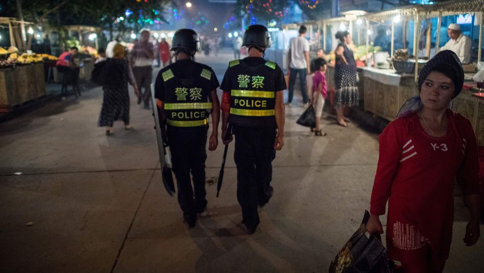 Police patrol a night food market near the Id Kah Mosque in Kashgar in Chinas Xinjiang Uighur Autonomous Region.