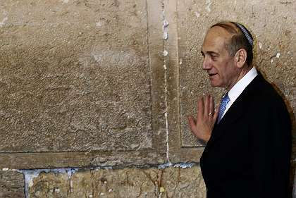 Israeli interim Prime Minister Ehud Olmert touches the Western Wall, Judaism's holiest prayer site, in Jerusalem.