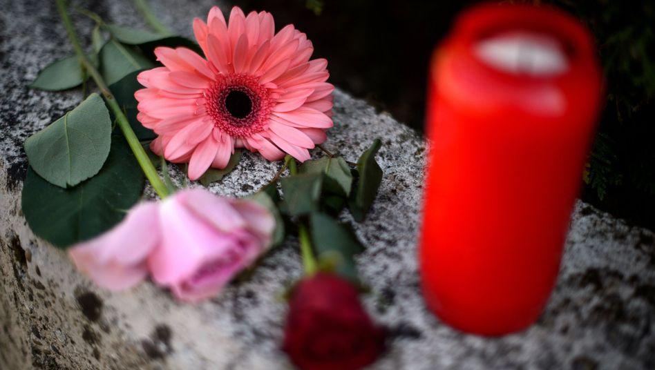 Blumen und Kerzen liegen auf einer Mauer vor dem Haus, in dem ein Siebenjähriger tot aufgefunden wurde