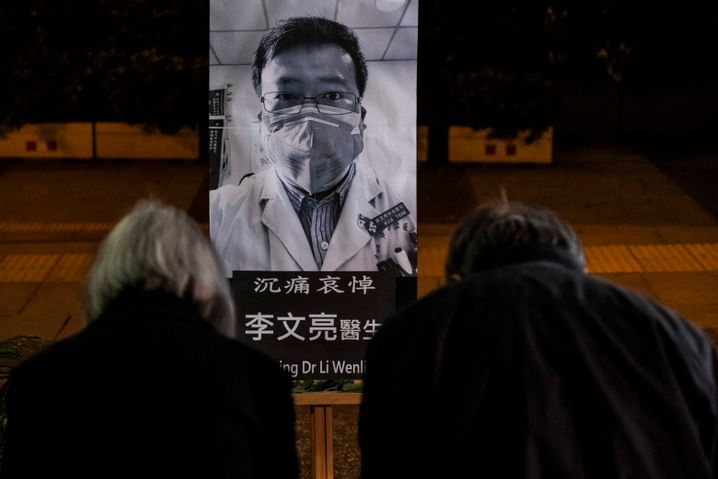 """People pay respect at a memorial to Dr. Li Wenliang: """"There should be more than one voice in a healthy society."""""""