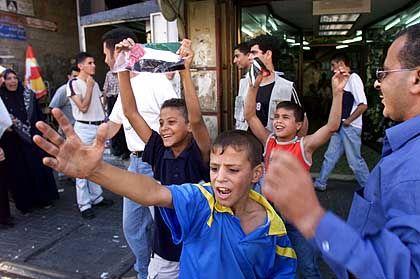 Kinder feiern vor der Kamera die Attentate - im Hintergrund eilen unbeteiligte Passanten vorbei