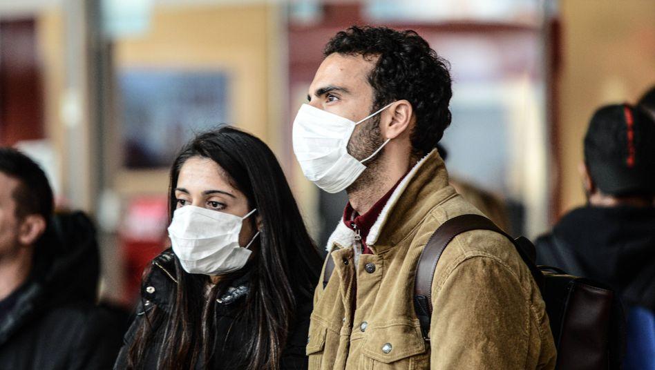Zwei Passanten im italienischen Turin tragen Atemschutzmasken: In Italien ist der sechste Mensch an Covid-19 gestorben