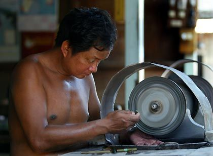 A man grinds jade stones at a market in Mandalay, Burma.