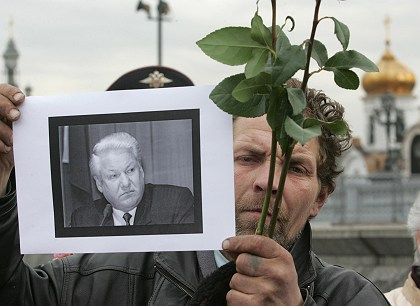 A man holds a portrait of the late former Russian President Boris Yeltsin as he stands in line to pay his last respects at Yeltsin's coffin in Moscow Tuesday.
