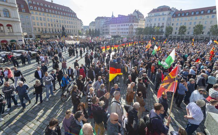 Teilnehmer einer Kundgebung von Pegida und Teilnehmer von Gegenkundgebungen stehen auf dem Altmarkt, dem ältesten Platz in Dresden