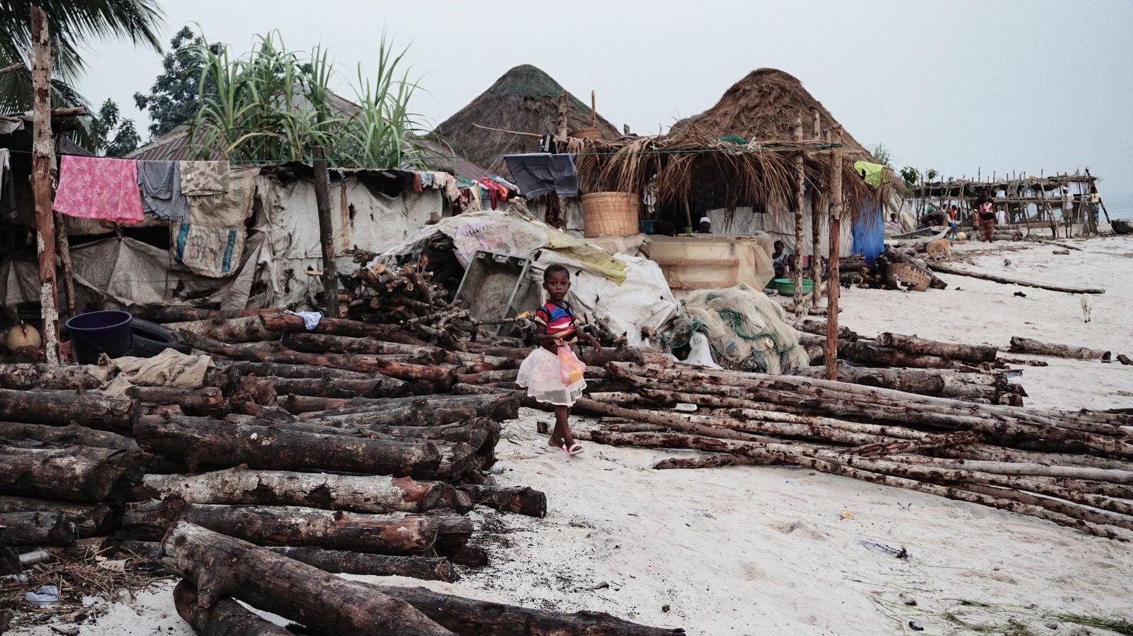 Ein Mädchen steht zwischen gestapeltem Feuerholz - Saidu Bah