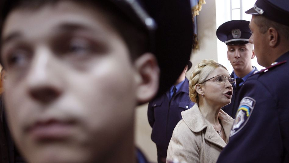 Yulia Tymoshenko addresses the media, surrounded by Interior Ministry officers, during a session at a court in Kiev (October 2011 photo).