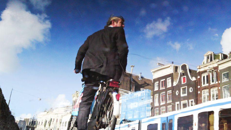 Ein Radler in Amsterdam: Für viele Niederländer ist das Pendeln zur Arbeit auf dem Fahrrad schon seit Jahren eine Selbstverständlichkeit