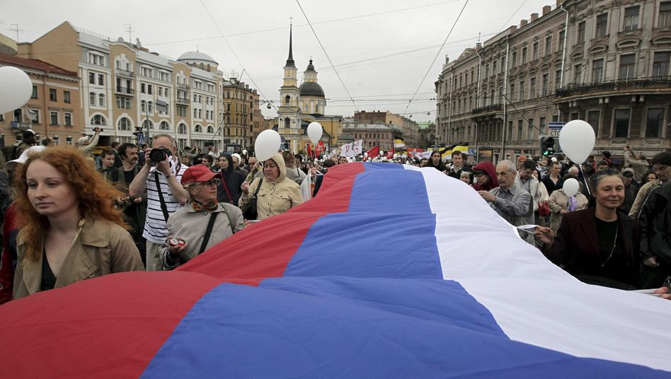 Demonstrators carry a huge Russian flag as they parade during an opposition rally 'For Russia without Putin!' in St. Petersburg in June.