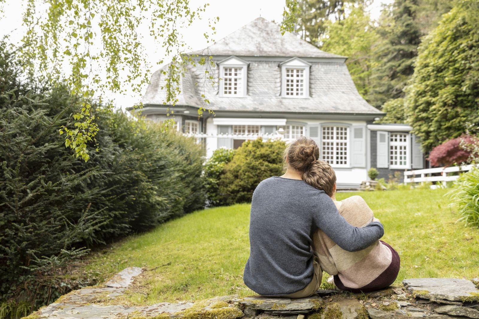Rear view of couple sitting on a wall in garden model released Symbolfoto property released PUBLICATIONxINxGERxSUIxAUTxH