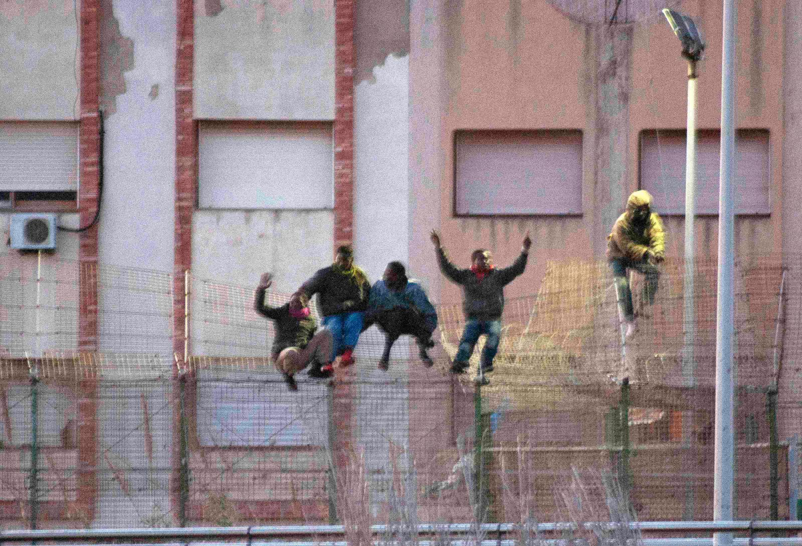 Immigrants scale over border fence separating Spain's north African enclave Melilla from neighboring Morocco