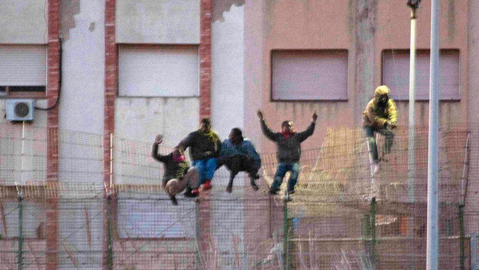 Menschen auf dem Grenzzaun zwischen der spanischen Exklave Melilla und Marokko