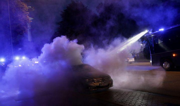 """Ein Wasserwerfer löscht nach der """"Welcome to hell""""-Demonstration ein ausgebranntes Auto"""