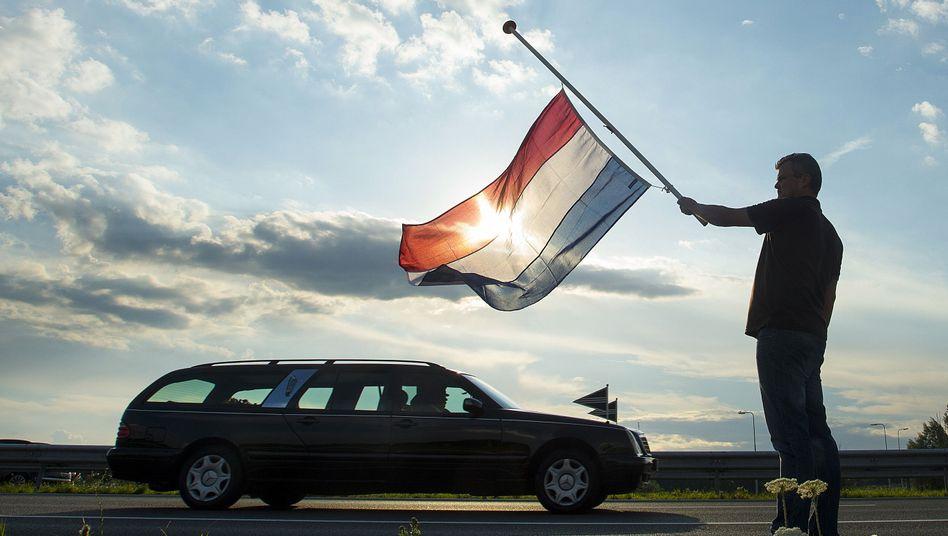 Trauer: Ein Niederländer schwenkt die Fahne, als Leichenwagen mit Opfern vorbeifahren