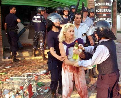 Polizisten nehmen eine Plünderin fest, die in Cordoba, einer Stadt nördlich von Buenos Aires, ein Geschäft ausräumte. Wegen der sozialen Missstände rumort es schon seit Jahren in argentinischen Städten