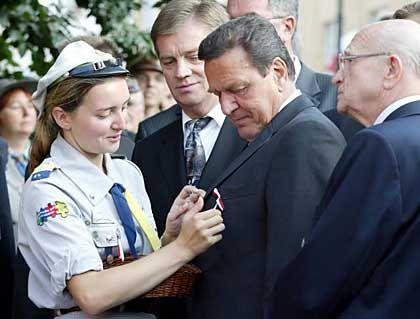 Vor der Kranzniederlegung: Schröder bekommt eine polnische Flagge ans Revers gesteckt