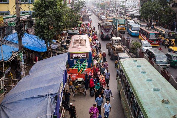 Textile workers walk along a busy street in Chittagong, Bangladesh.