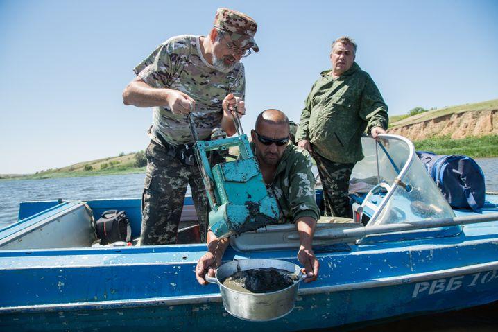 Sergej holt mit einem bestimmten Apparat vom Grund Schlick aus dem Wasser, Igor (m.) hilft ihm, hinten rechts Andrej