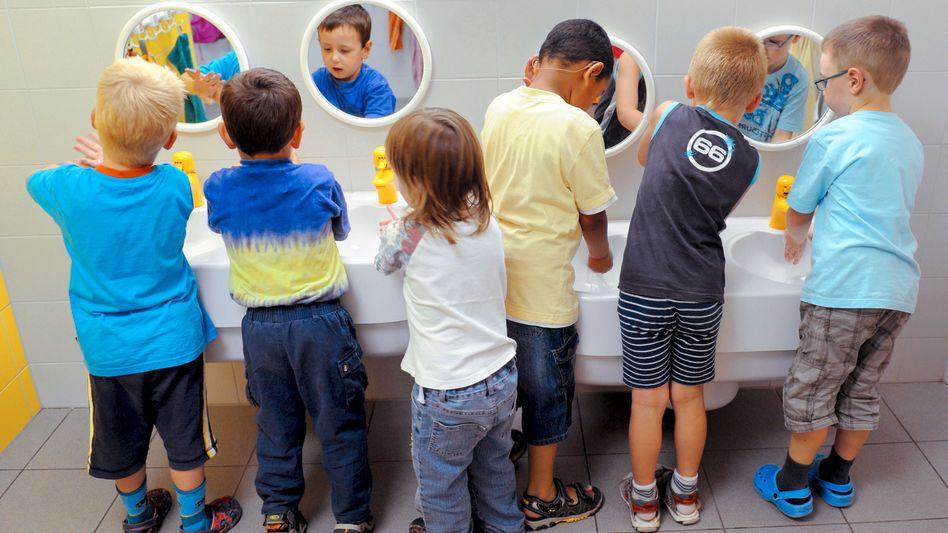 Children wash their hands at the Kinderland preschool in the eastern German city of Halle.