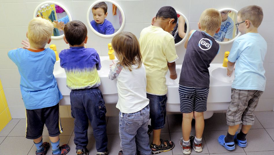 Children wash their hands at the Kinderland preschool in the eastern German city of Halle.