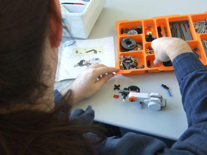 Ein Bewerber mit Autismus baut beim Softwarehersteller SAP in Walldorf an einem Lego-Roboter
