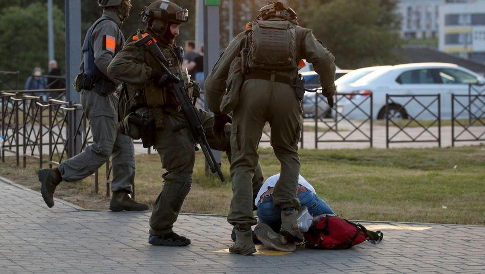 Polizisten in Kampfmontur treten einen am Boden liegenden Demonstranten in der belarussischen Hauptstadt Minsk