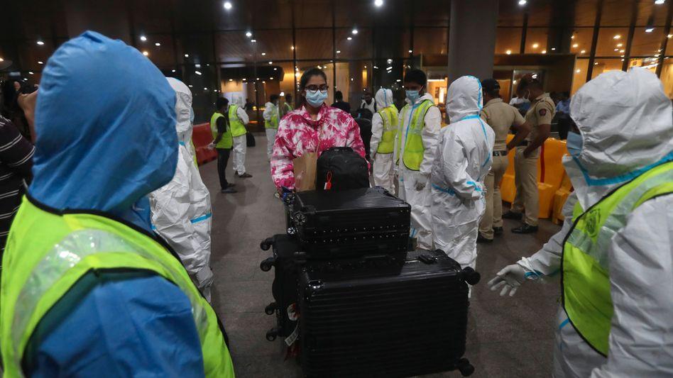 Passagiere aus Großbritannien werden am Flughafen von Mumbai von Arbeitern in Schutzanzügen empfangen