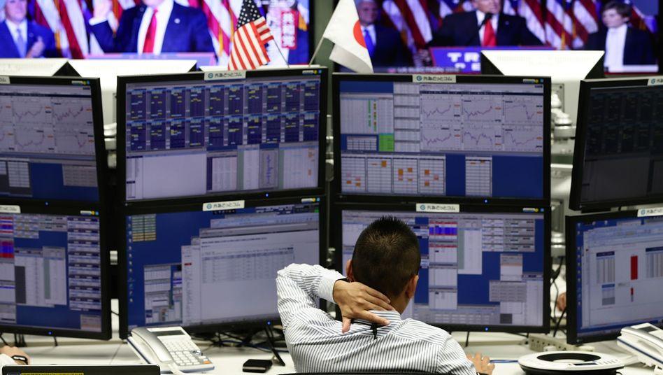 Ein Börsenhändler in Tokio schaut Trumps Siegesrede.