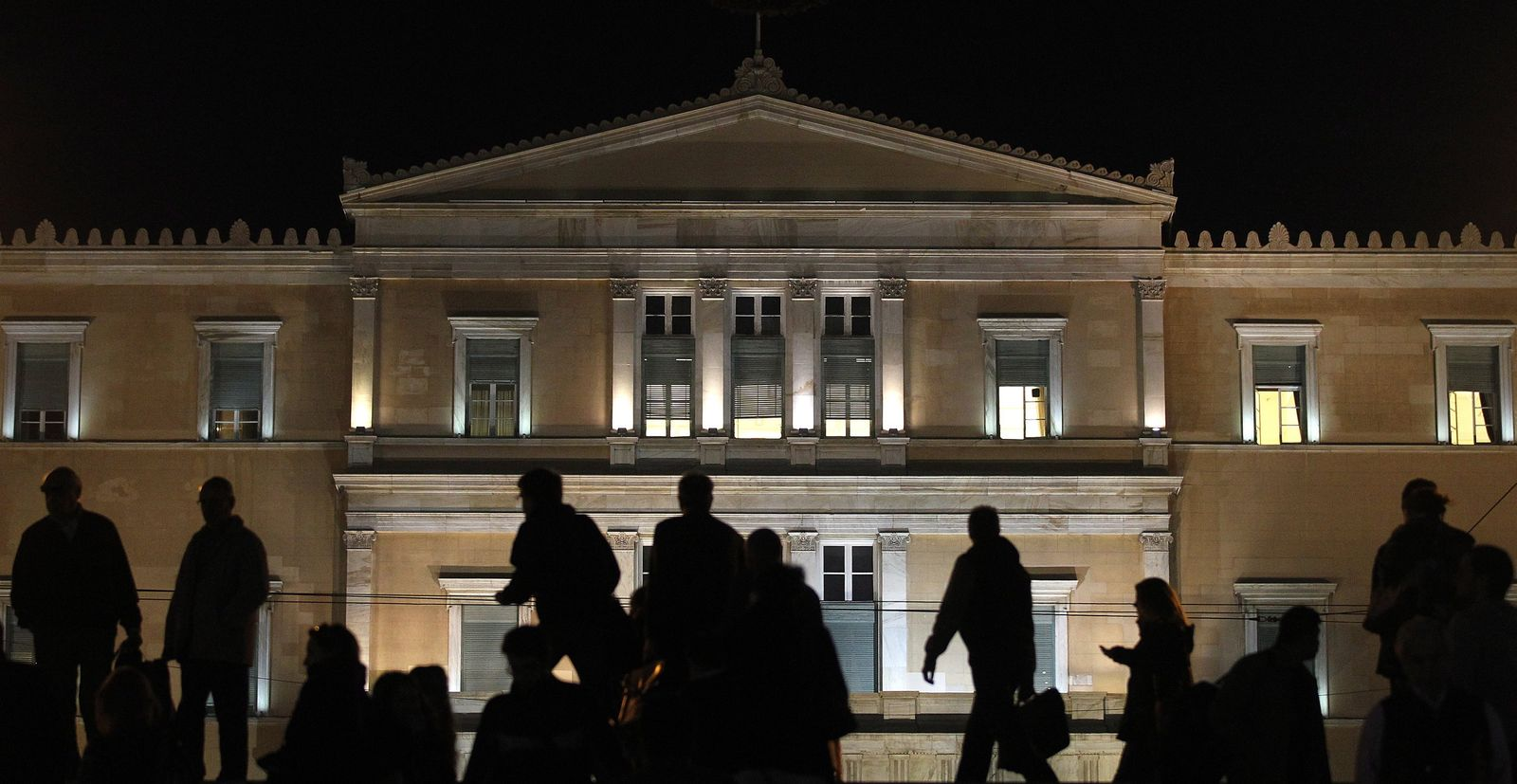 People walk in front of the Greek Parliament building in Athens