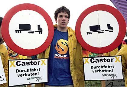 Ein Greenpeace-Aktivist demonstriert mit selbst gebauten Verkehrsschildern in Splietau bei Dannenberg, Niedersachsen