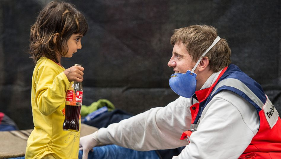 "A Red Cross volunteer plays with a Syrian refugee at a shelter in the state of Baden-Württemberg: ""Germany has become diverse."""