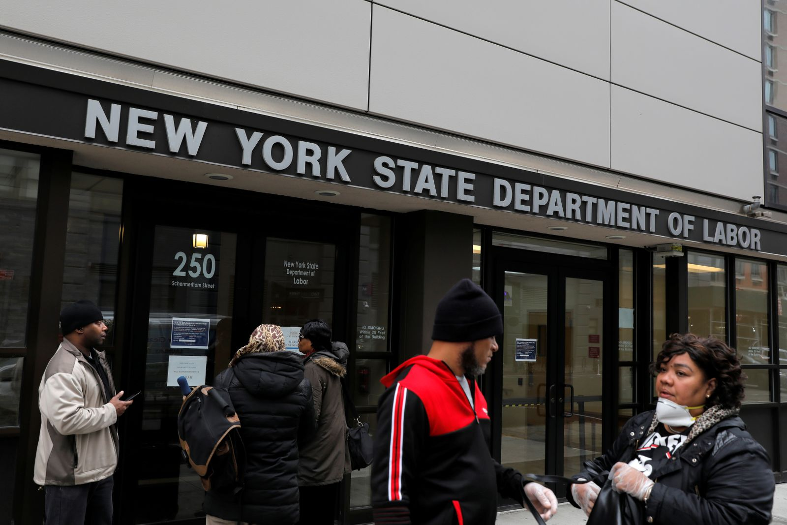 People gather at the entrance for the New York State Department of Labor offices, who closed to the public due to the coronavirus disease (COVID-19) outbreak in the Brooklyn borough of New York City