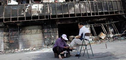Der Alltag kehrt zurück nach Ürümqi: Eine Schuhputzerin arbeitet vor einem ausgebrannten Haus