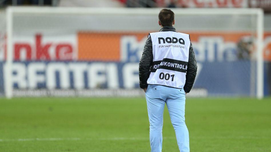 Ein Vertreter der Dopingkontrolle steht bei Spielschluss auf dem Rasen.