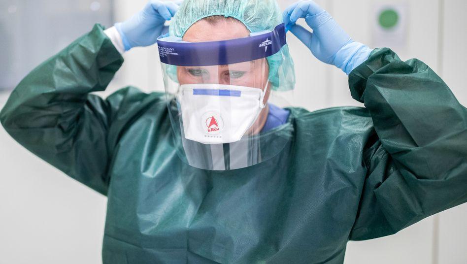 Eine Stationsleiterin auf der Infektionsstation der Uniklinik Essen in Schutzkleidung