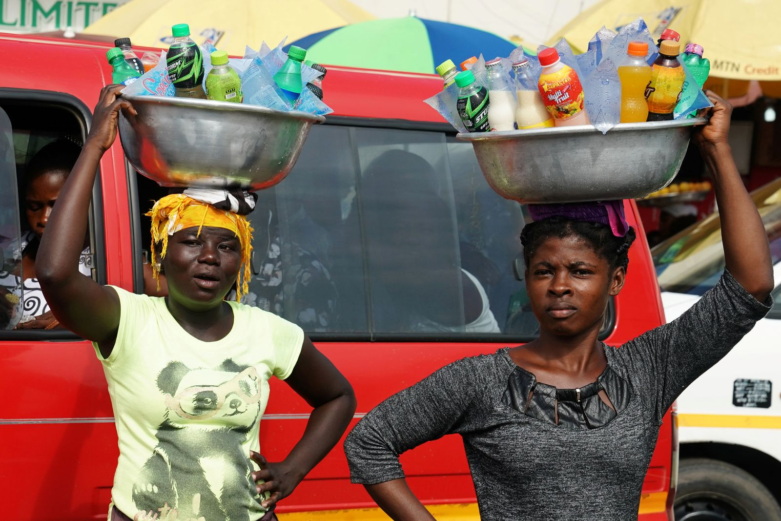 Women carrying drinks on their heads watch as the motorcade that carries the media covering U.S. first lady Melania Trump passes in Accra
