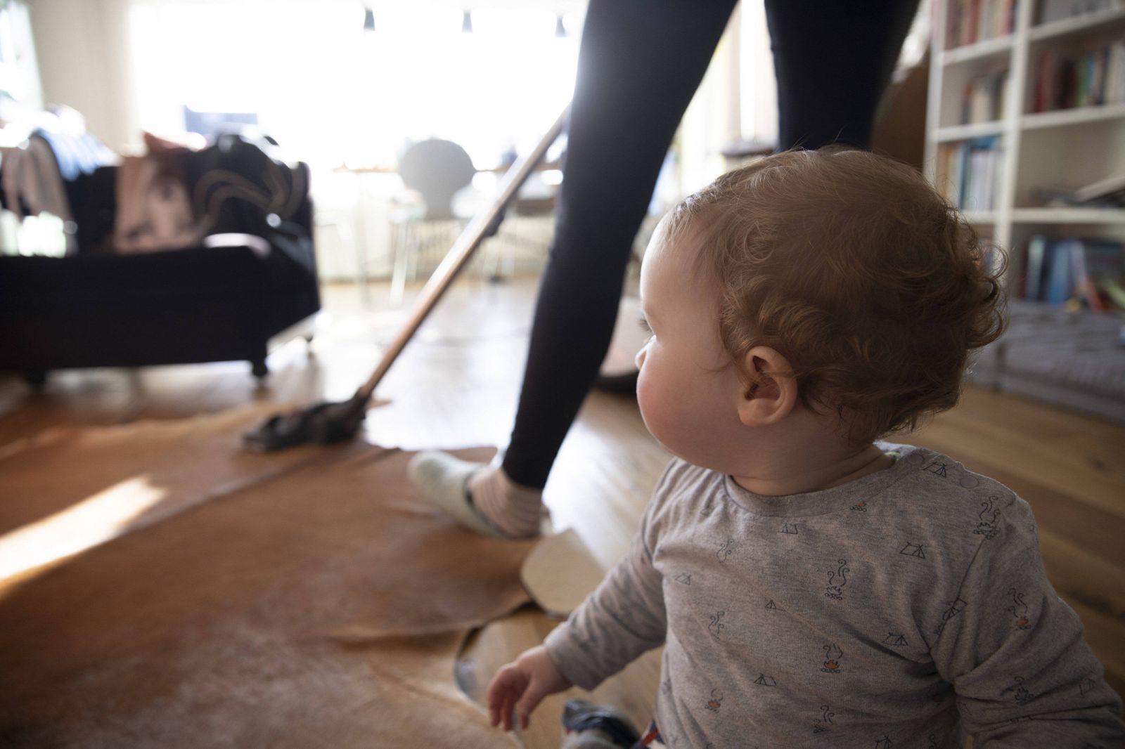 Frau saugt Staub mit einem Staubsauger in ihrem Wohnzimmer, Bonn, 19.12.2019. Woman vacuuming with a vacuum cleaner in h