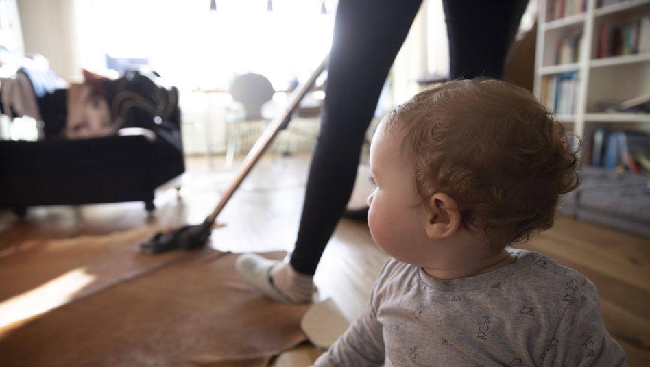 Eine Frau saugt Staub: Vor allem wenn das erste Kind da ist, nimmt die Gleichstellung in Beziehungen ab