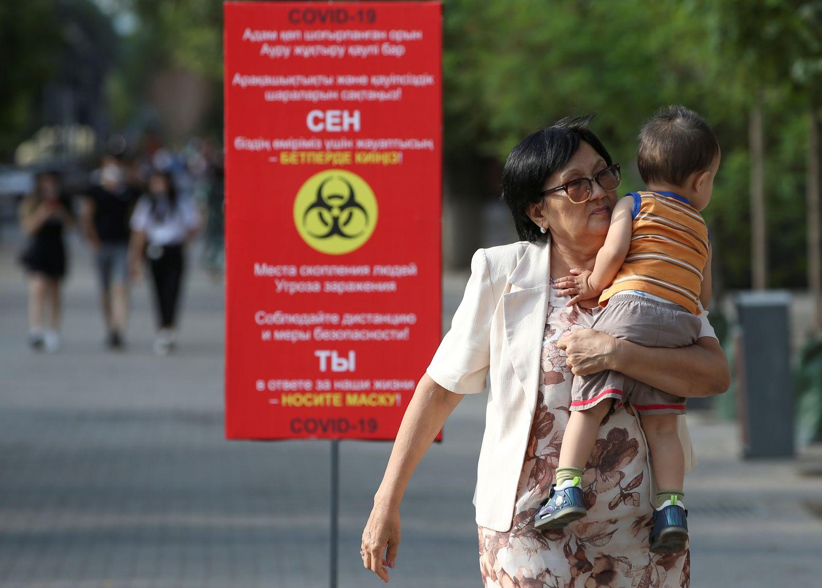 People walk past a board informing of preventive measures against the coronavirus disease in Almaty