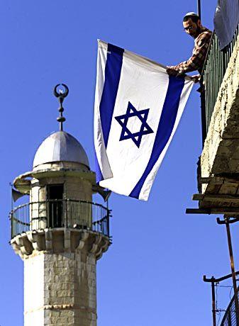 Ein Siedler hisst die israelische Flagge in Jerusalems Altstadt