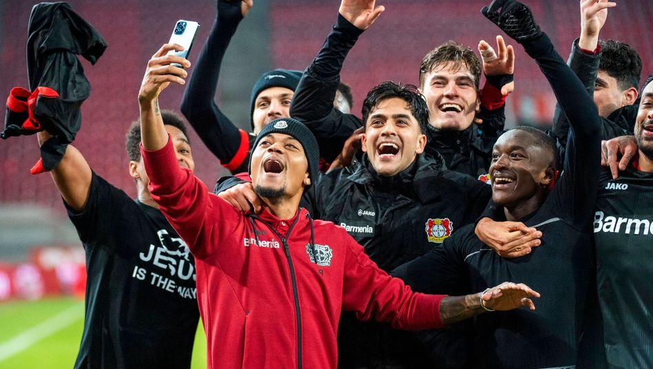 Leon Bailey (vorn mit Handy) feiert mit seinen Teamkollegen von Bayer Leverkusen das 4:0 in Köln