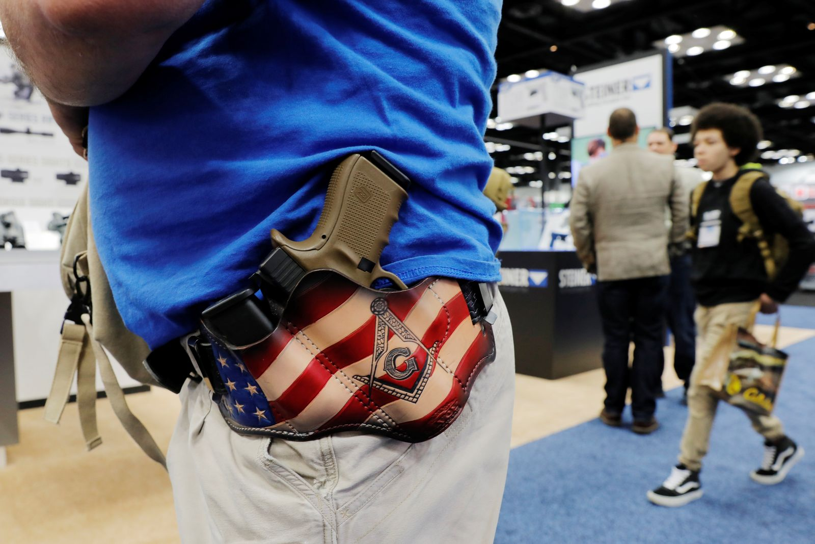 A man carries his Glock handgun in a custom designed holster during the National Rifle Association (NRA) annual meeting in Indianapolis, Indiana