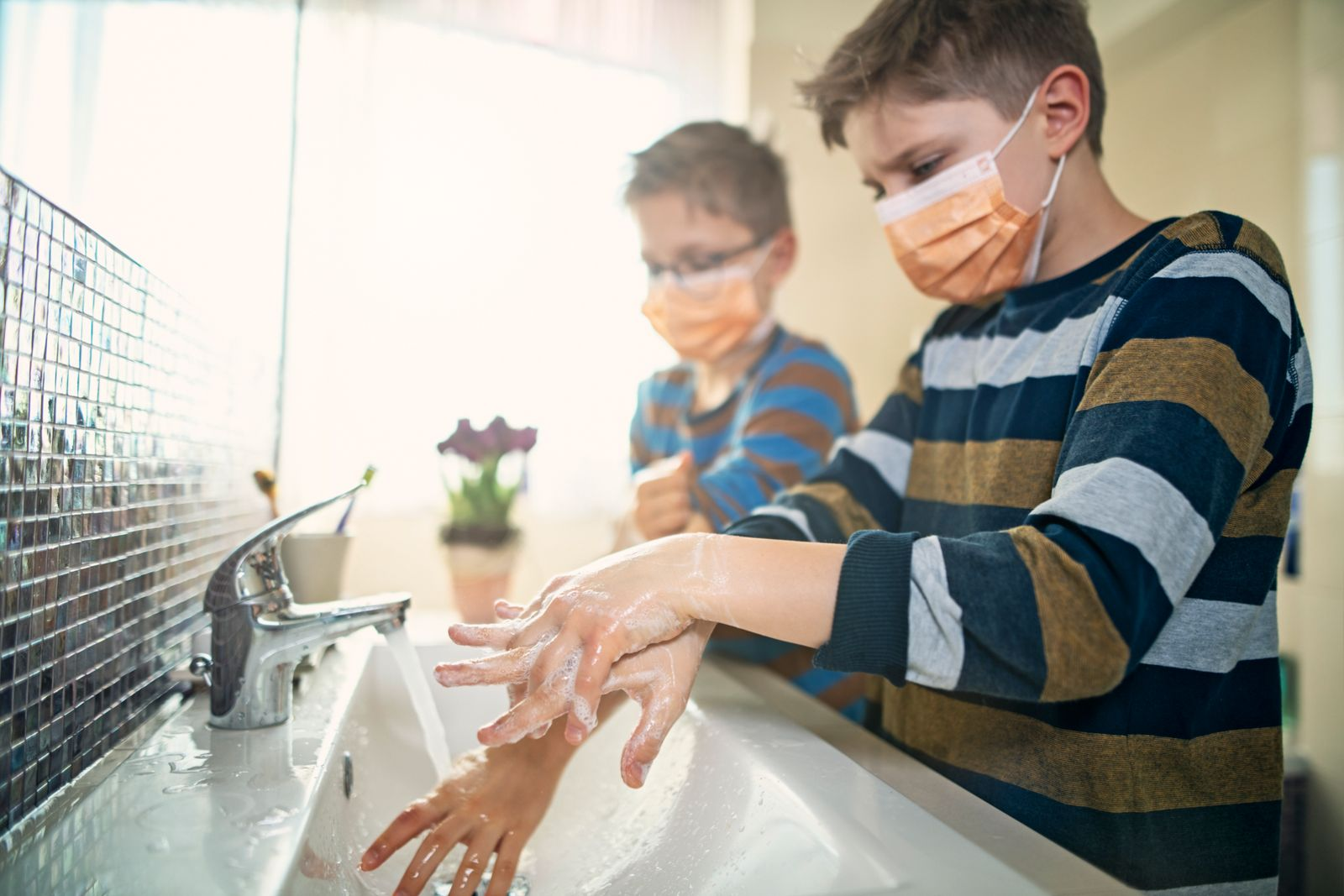 Little boys wearing face masks washing hands thoroughly