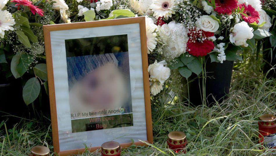 Blumen, Grablichter und Porträts der Getöteten stehen am Tatort im Niddapark
