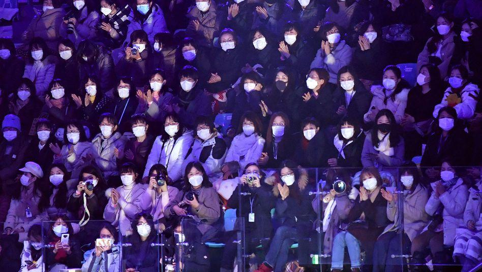 Zuschauer mit Mundschutz beim Eisskating in Seoul: So ähnlich könnte es auch im Fußballstadion aussehen