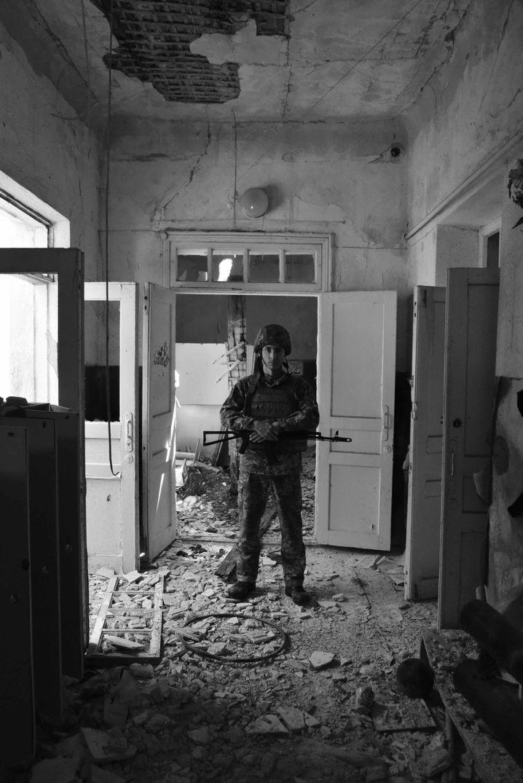 Ein ukrainischer Soldat steht in einem zerstörten Kindergarten.